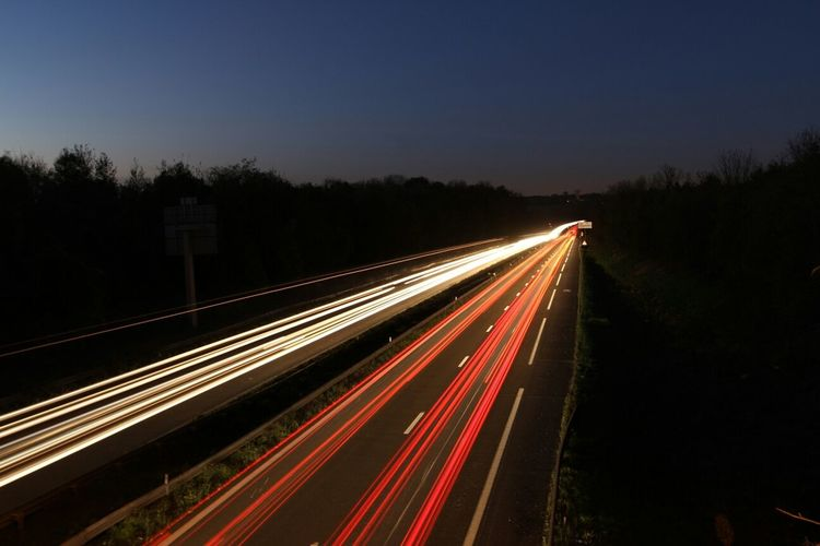 Illuminated light trail on road against clear sky at night