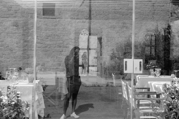 Reflection of woman photographing while standing at outdoor cafe