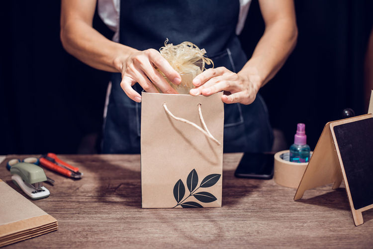 Midsection of woman packing gift on table