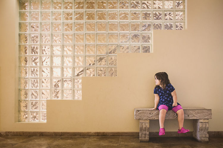 Full Length Of Girl Sitting Against Wall