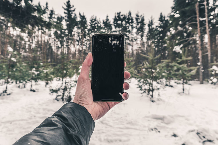 Close-up of hand holding smart phone against snow covered trees