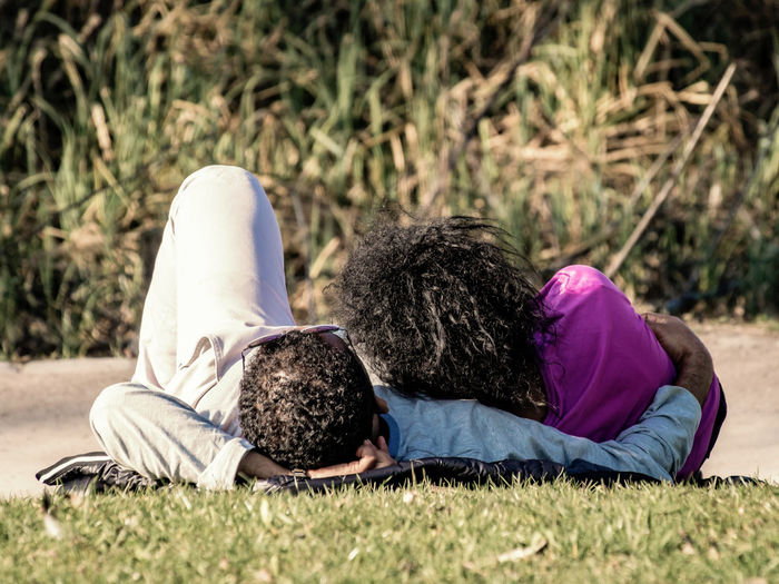 Couple relaxing on grassy field