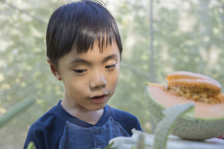 Close-Up Of Boy With Melon Outdoors