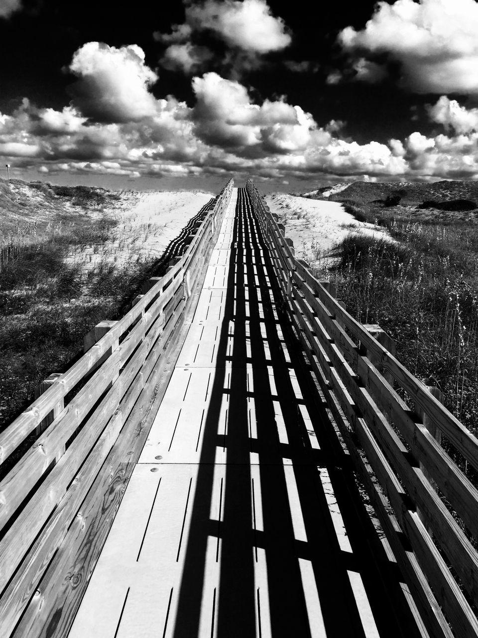Boardwalk Leading Towards Beach On Sunny Day