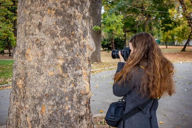 Side view of woman photographing by trees in park