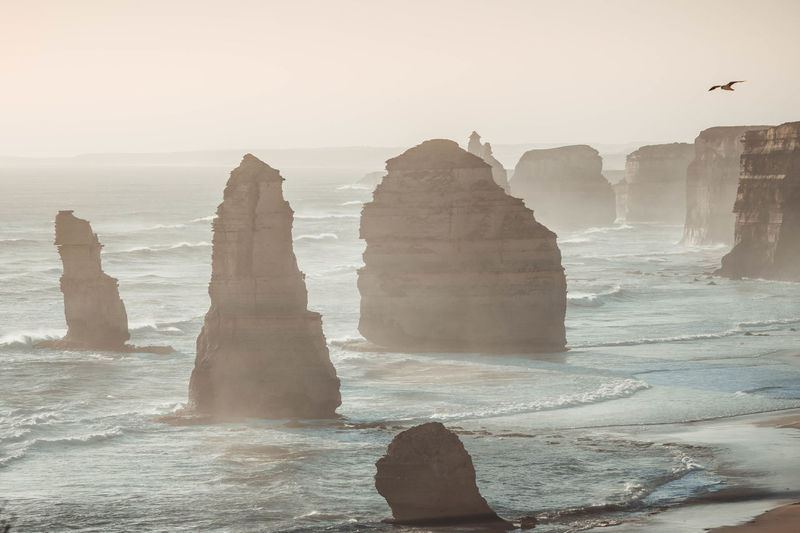 The twelve apostles in sea against clear sky during foggy weather