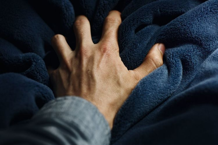 Cropped image of hand on blanket