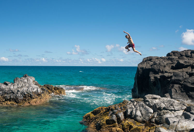 Low angle view of shirtless man jumping in sea from cliff against sky