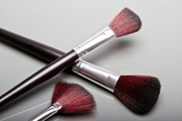 Makeup brushes on gray surface Beauty Beauty Product Blush - Make-up Body Care And Beauty Brush Choice Close-up Fashion Hygiene Indoors  Lipstick Make-up Make-up Brush No People Personal Accessory Red Self Improvement Still Life Studio Shot Table Two Objects Variation