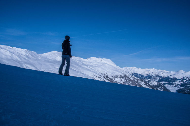 Woman standing on snowcapped mountain against sky