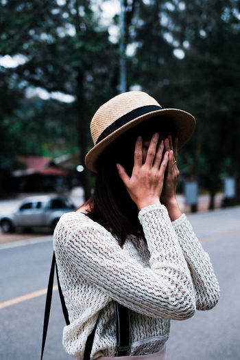Midsection of woman wearing hat standing by tree in city