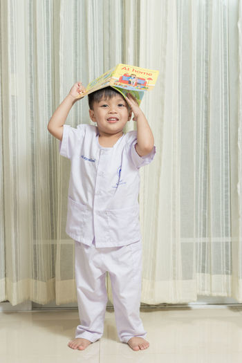 Portrait Of Boy Holding Book While Standing Against Curtain At Home