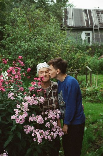 Young woman kissing grandmother on cheek in yard