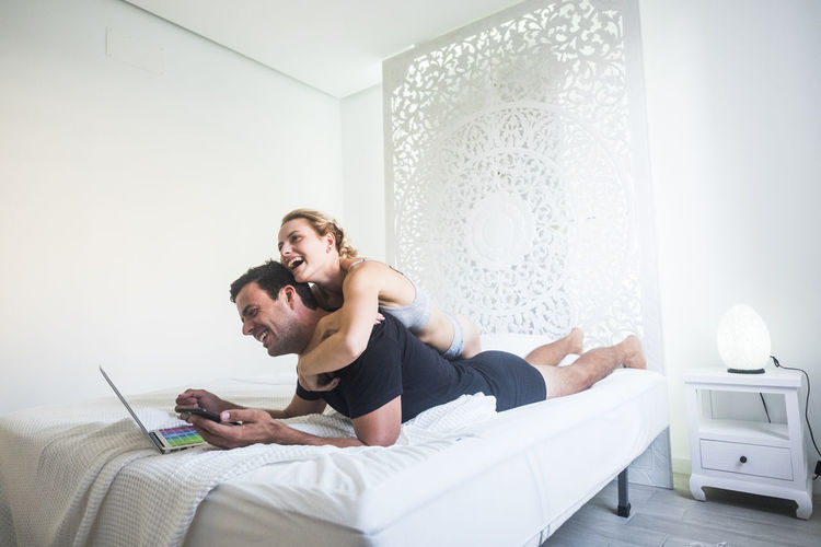 Smiling woman embracing man using mobile phone and laptop while lying on bed at home