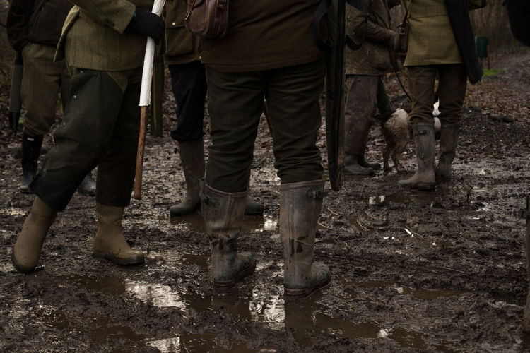 Low Section On People Wearing Rubber Boots On Wet Muddy Field