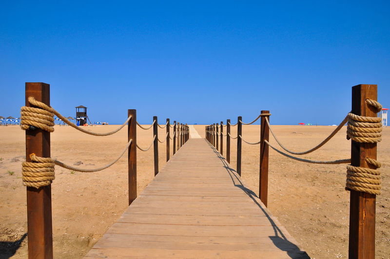 View of wooden walkway against clear blue sky