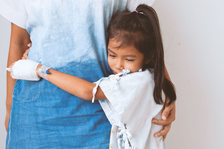 Girl embracing mother against wall in hospital