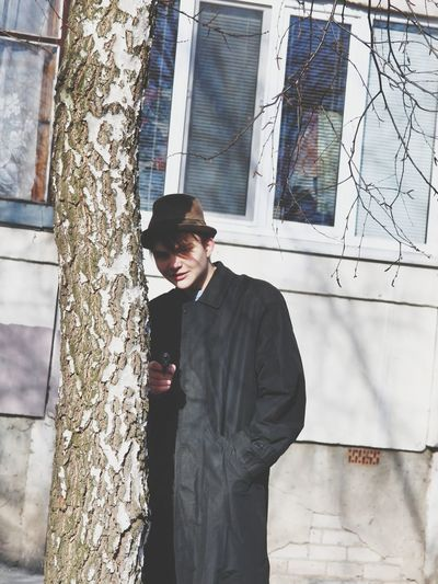 Young man wearing hat and overcoat while standing by tree trunk in city