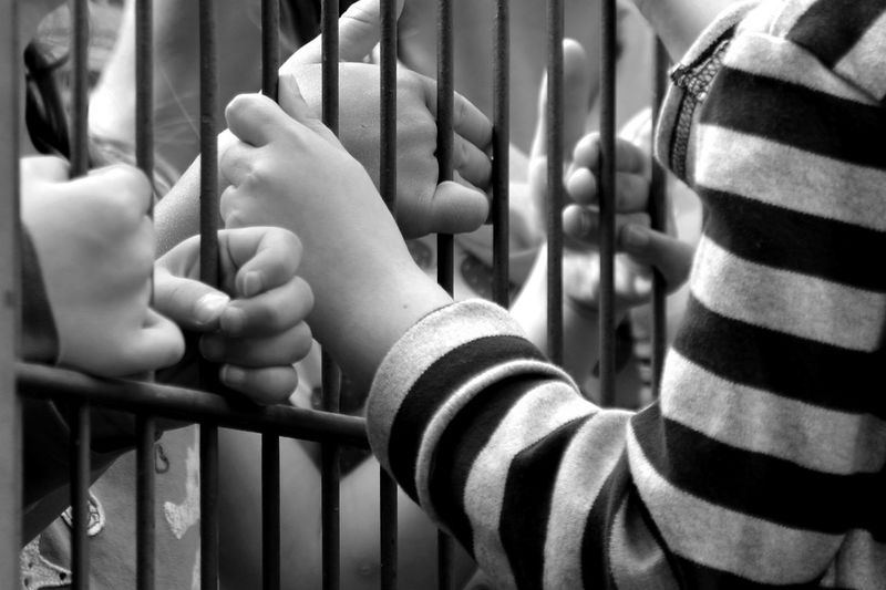 Cropped hands holding metal gate