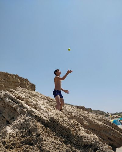 Low angle view of shirtless boy catching ball on rocky shore against clear blue sky