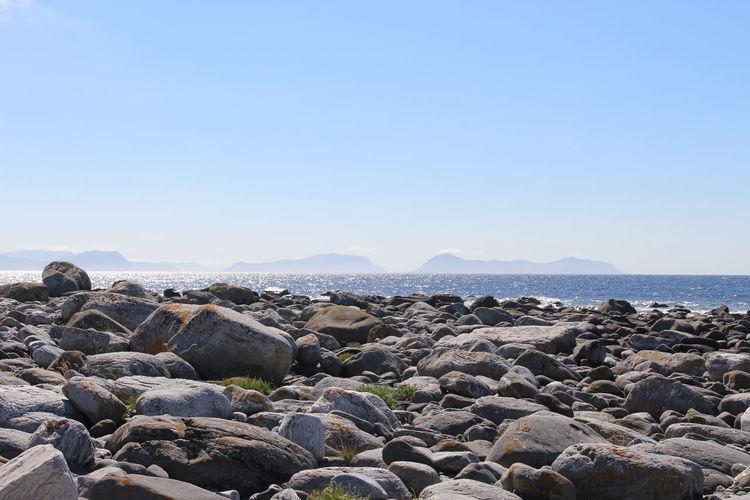Rocks on beach against clear sky