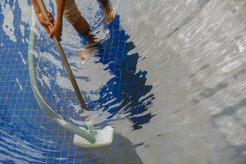 Low section of man cleaning swimming pool with vacuum cleaner