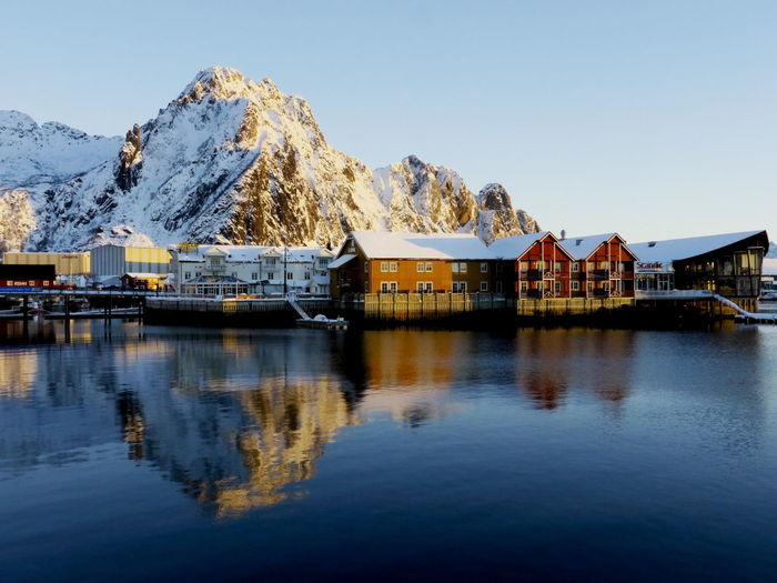 Houses by snowcapped mountain and lake against clear sky