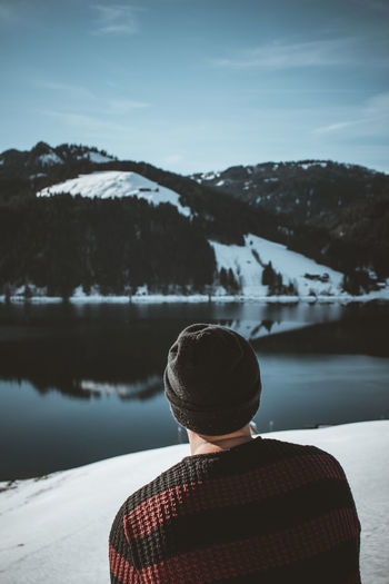 Rear view of person looking at snowcapped mountain against sky