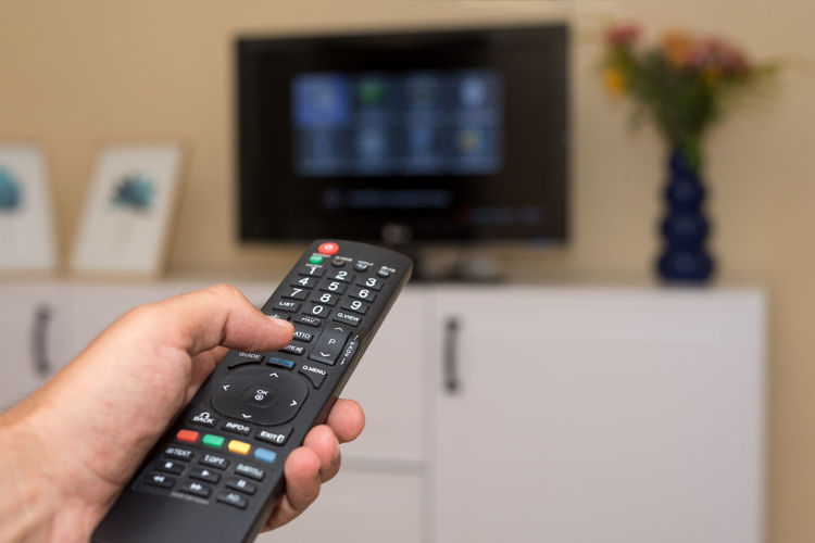 Arts Culture And Entertainment Changing Channels Choice Control Flat Screen Focus On Foreground Hand Human Body Part Human Hand Indoors  Keypad Liquid-crystal Display People Push Button Pushing Relaxation Remote Remote Control Technology Television Set Watching Watching Tv