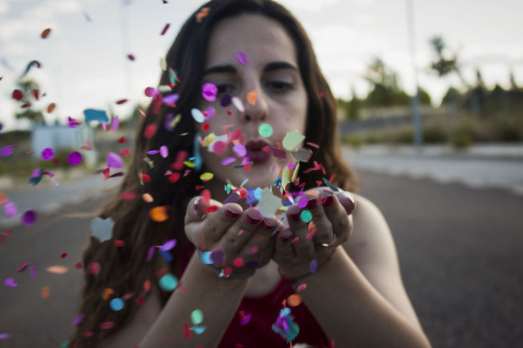 Close-Up Of Young Woman Blowing Confetti On Road