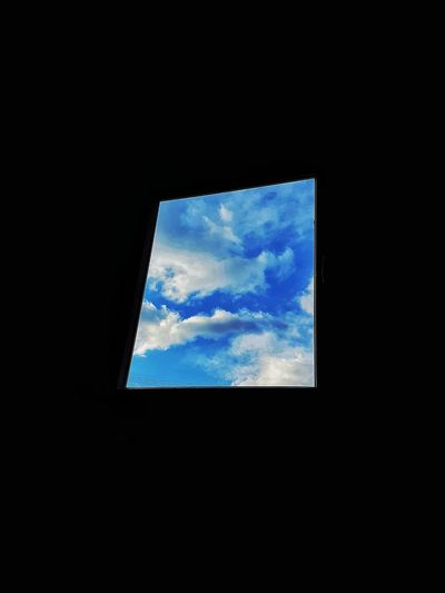 Low angle view of cloudy sky seen through window