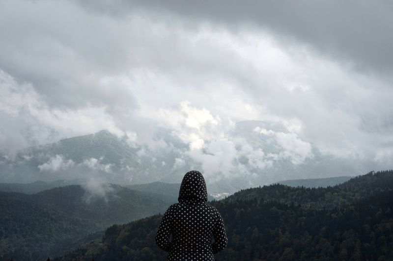 Rear View Of Mid Adult Woman Looking At Mountain Range While Standing Against Cloudy Sky