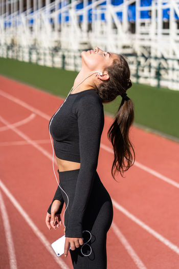 Woman listening music over phone on running track