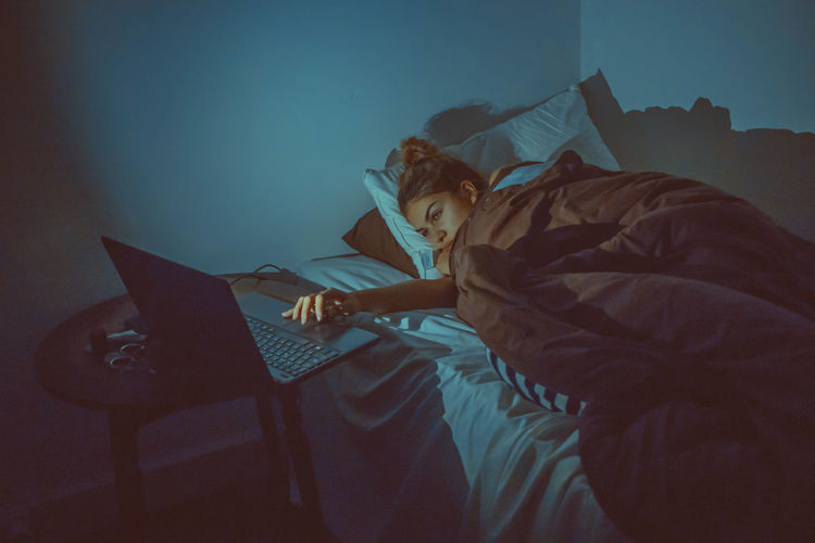 High angle view of woman using laptop while lying on bed at home