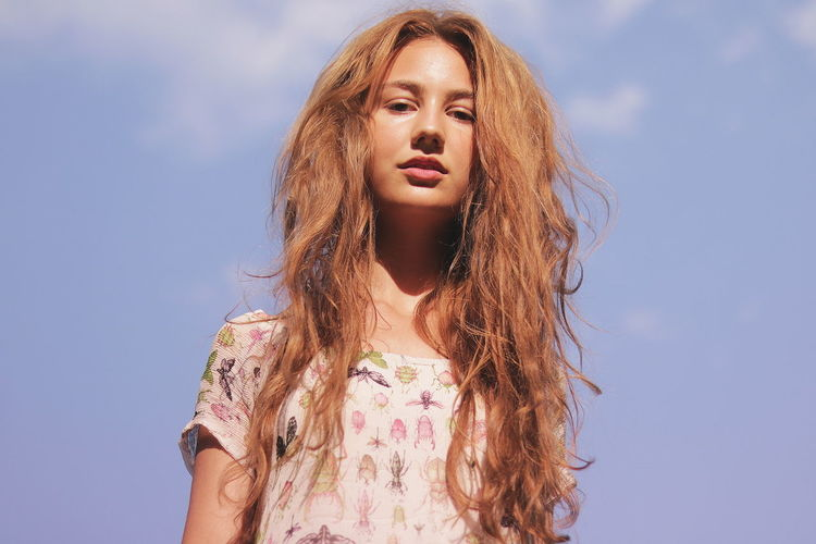 Low angle portrait of young woman with messy hair against sky