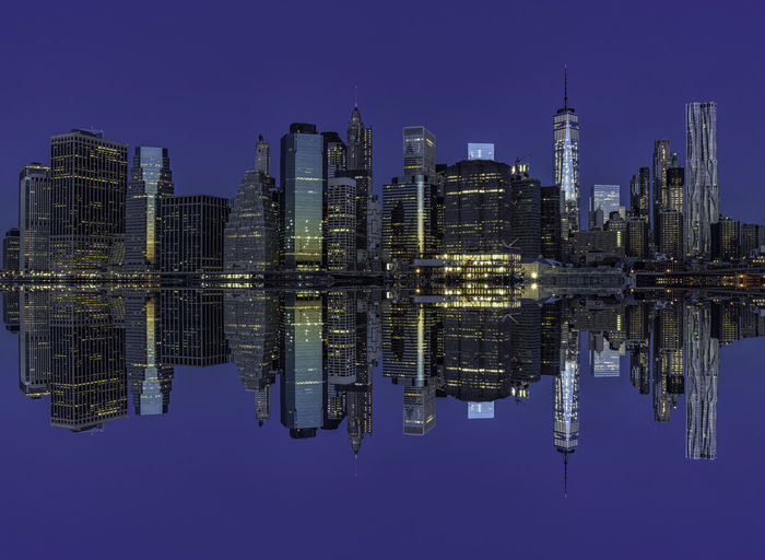 Illuminated Manhattan Skyline Reflection In East River At Night