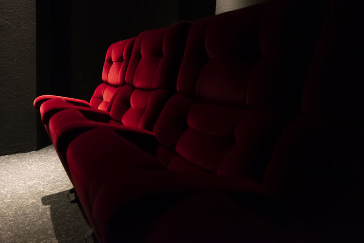 Red Cinema Chair. Theater Absence Abundance Armchair Arts Culture And Entertainment Chair Cinema Close-up Comfortable Dark Empty Furniture Illuminated In A Row Indoors  Many Movie Theater No People Red Relaxation Seat Side By Side Sofa