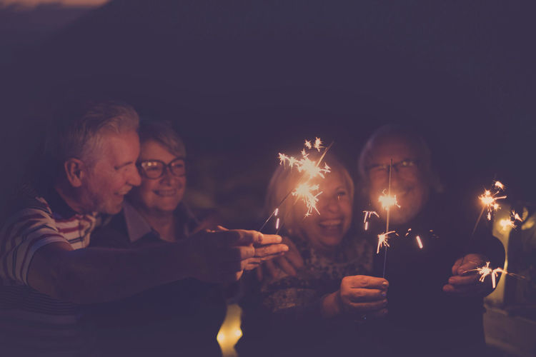 four aged people having party by night Adult Bonding Burning Candle Celebration Embracing Family Flame Friendship Fun Happiness Illuminated Lifestyles Men Night Outdoors Party - Social Event Photographing Real People Retired Person Senior Couple Smiling Sparkler Togetherness Women