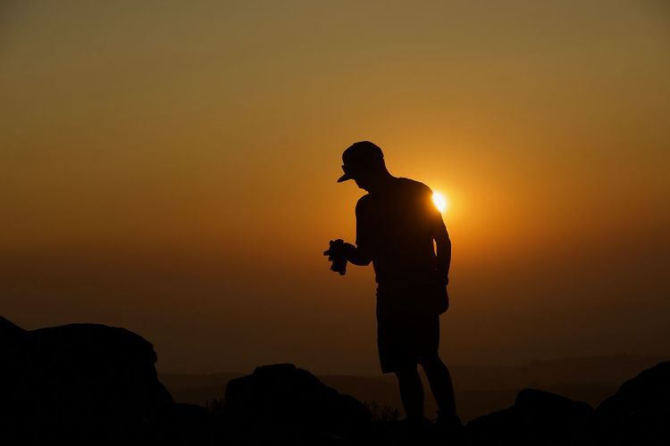 Silhouette man photographing while standing on mountain against sky during sunset