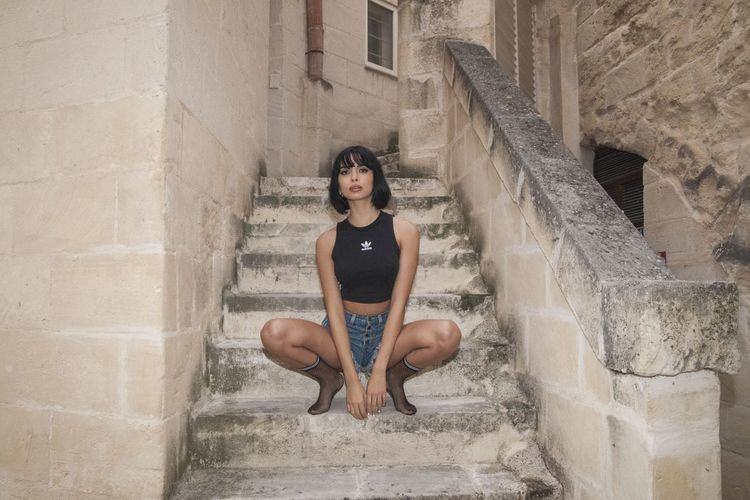 Young woman sitting on staircase