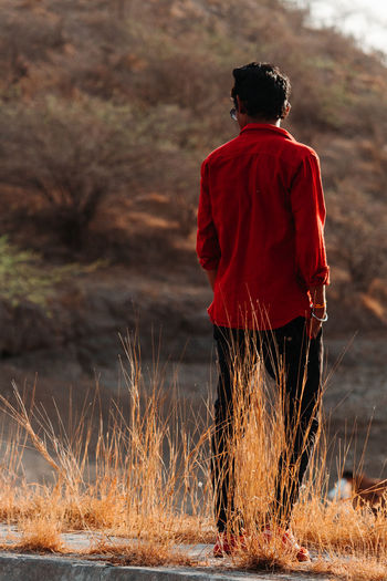 Rear View One Person Real People Men Nature Standing Red Lifestyles Land Casual Clothing Water Focus On Foreground Day Full Length Leisure Activity Plant Field Outdoors