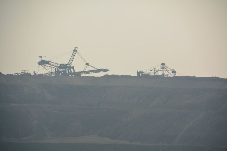 Machinery at coal mine against clear sky