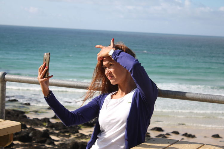 Woman taking selfie at beach on sunny day