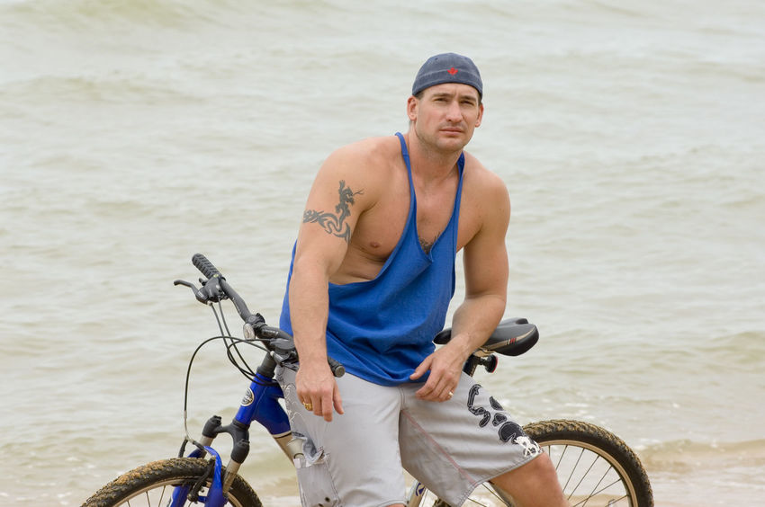 Young muscle man sitting on his bicycle at beach in Thailand Athletic Baseball Cap Beach Bicycle Caucasian Appearence Handsome Leisure Activity Lifestyles Looking At Camera Macho Masculinity Muscular Build Ocean Outdoors Person Photo Photography Portrait Real People Sea Sitting Sportswear Standing Tattoo Thailand Young Adult Young Man