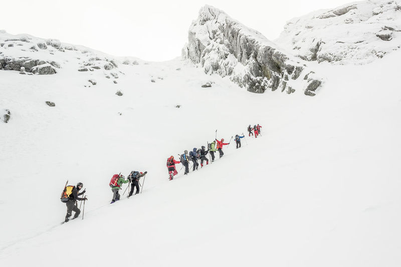 Low Angle View Of Hikers Climbing Snow Covered Mountain