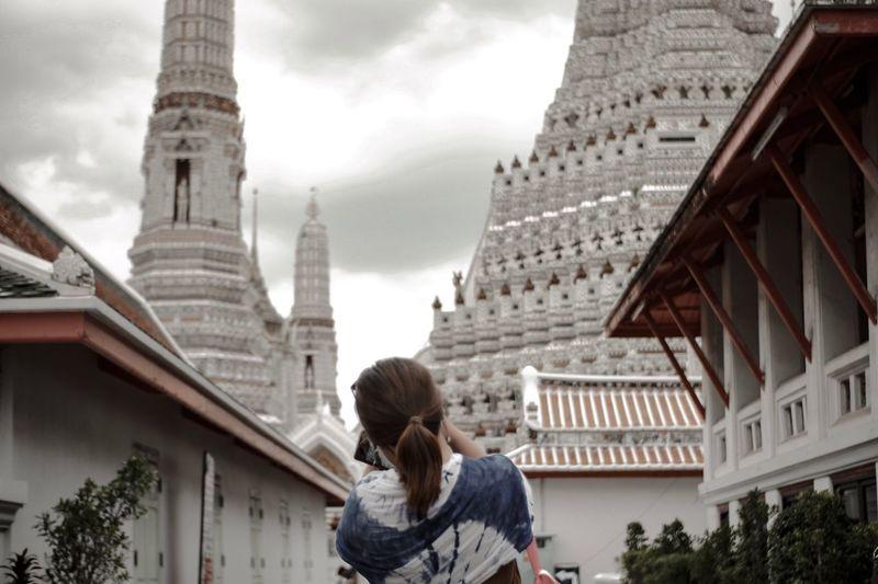 Rear view of woman walking against buildings in city