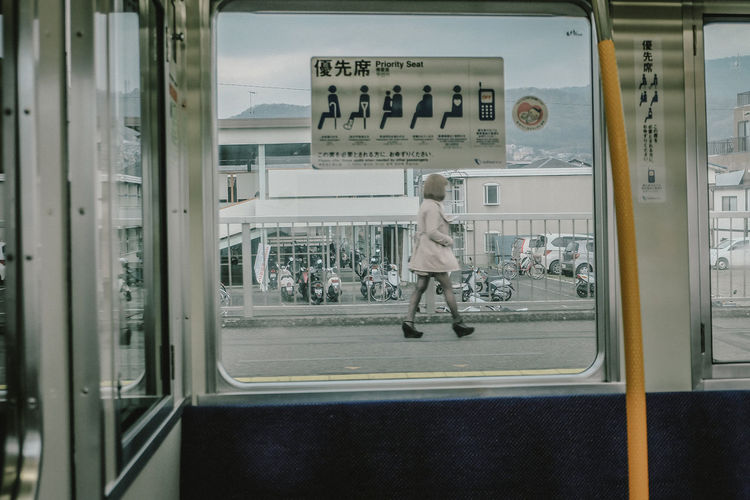 The window train with women. Window Train Waiting Outdoors Leisure Activity Railroad Station Architecture City Rail Transportation Travel Text Day Lifestyles Mode Of Transportation Window Glass - Material Men People Transportation Public Transportation Transparent Full Length Real People Streelife Still Life