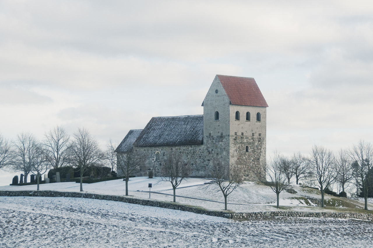 Built Structure With Bare Trees On Snow Landscape
