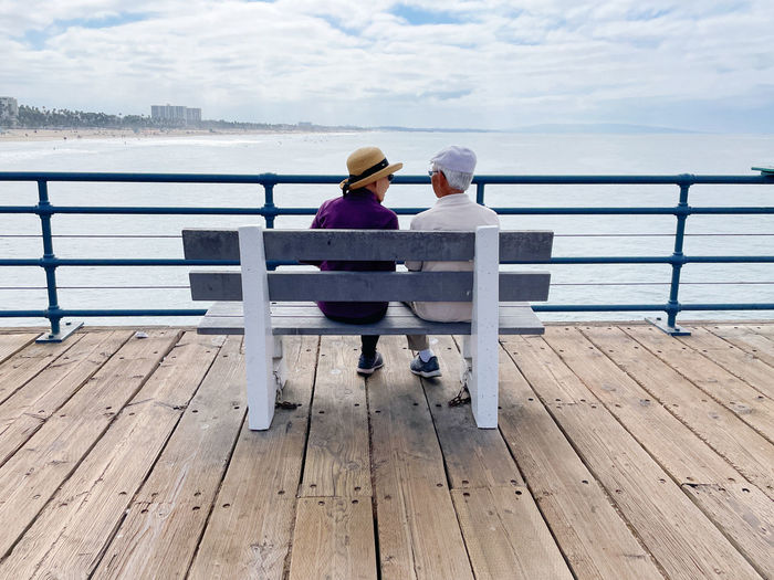 Rear view of people sitting on railing against sea