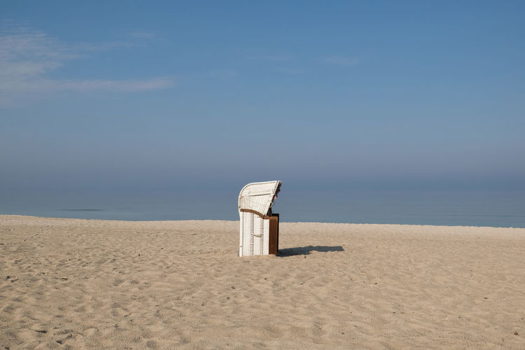 Hooded Beach Chair On Sand Against Sky During Sunny Day